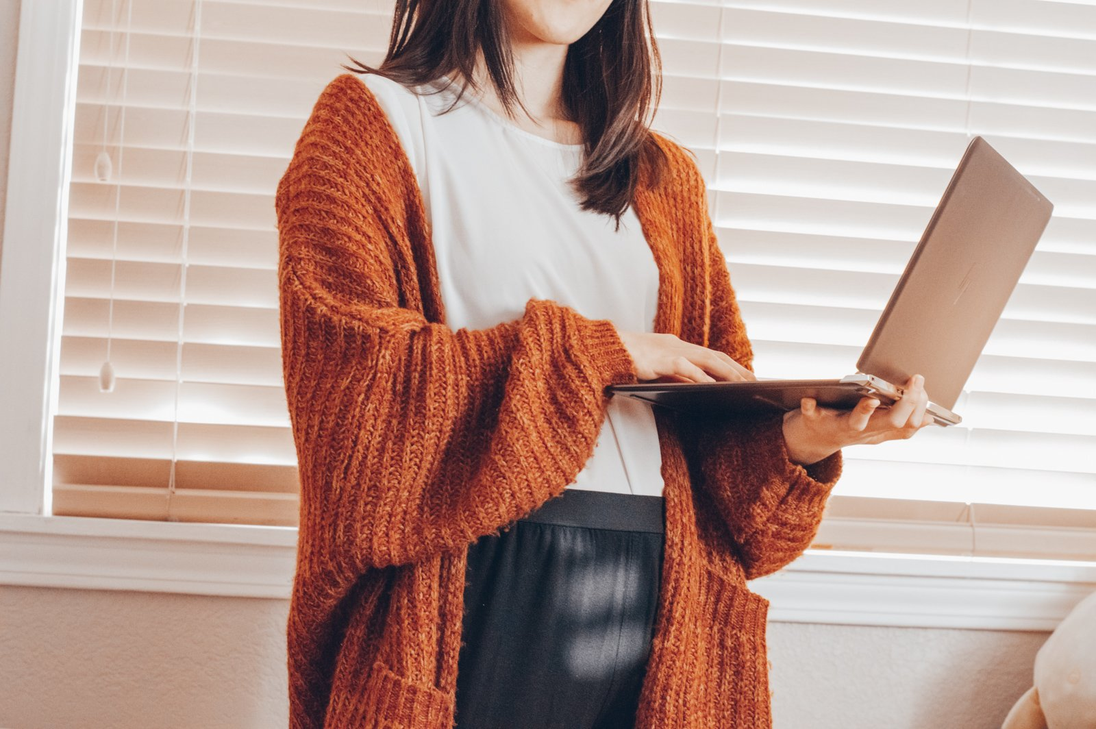 Girl wearing cardigan holding laptop