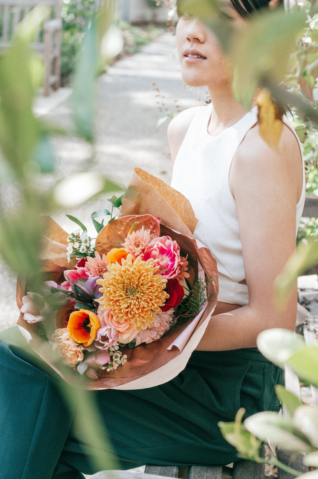 Girl sitting and holding a bouquet of flowers
