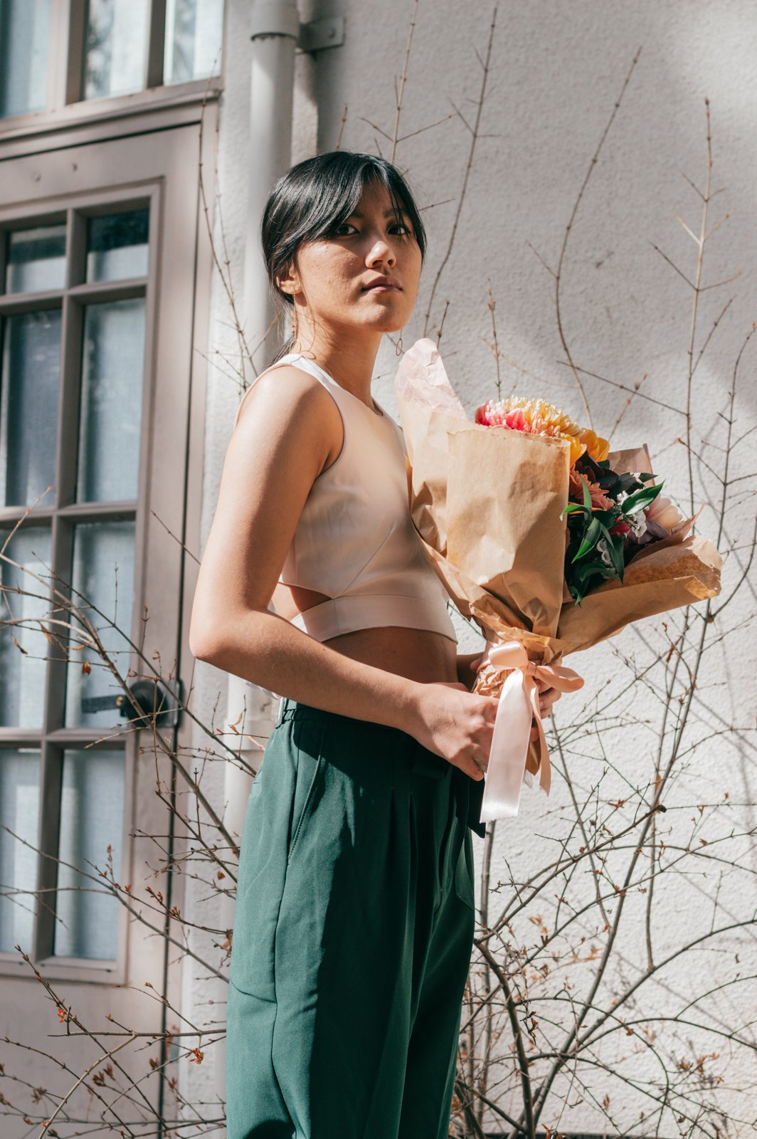 white top and green pants with bouquet